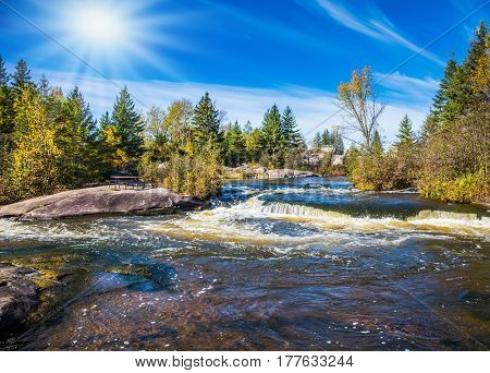 Foamy water rifts on smooth stones and low fir-trees on river banks Winnipeg. Autumn northern sun in Old Pinava Dam. The concept of ecological and extreme tourism