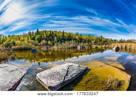 Indian summer in Manitoba, Canada. Old Pinawa Dam Park. The concept of ecological and recreational tourism. Incredible cirrus clouds over the Winnipeg River