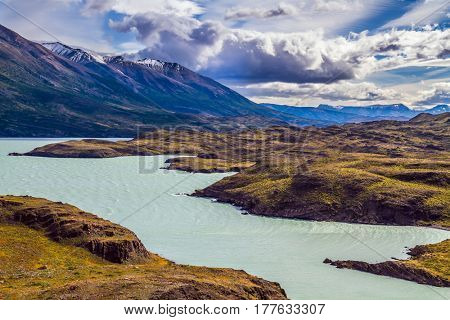 Azure lake Pehoe between rocks Los Kuernos. National Park Torres del Paine. Travel in Chile. The concept of active and extreme tourism
