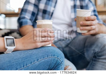 Time for coffee. Close up of a plastics cup filled with coffee and being held by nice pleasant woman while enjoying her break from work