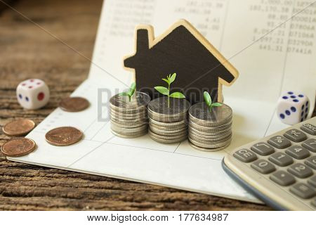 stack coins and house wood model green plant growthconcept idea for save and growth money