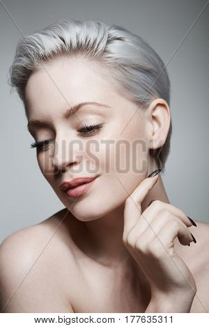 Portrait of sensual young woman with short hair looking down.