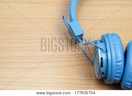 Blue headphones on wooden background ,easy listening concept with soft light style.