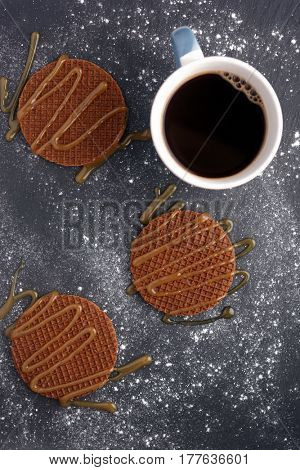 Stroopwafels with caramel sauce and a cup of black coffee on a slate surface