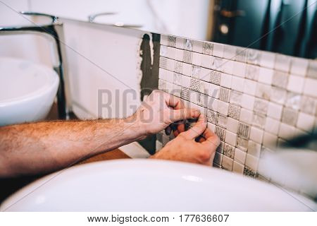 Close Up Details Of Industrial Worker Applying Mosaic Ceramic Pattern Tiles On Bathroom Shower Area.