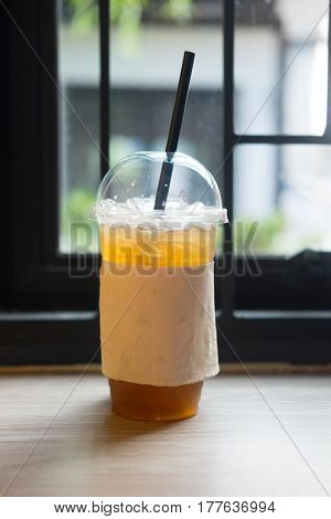 cup of ice lemon tea on wooden table in coffee shop