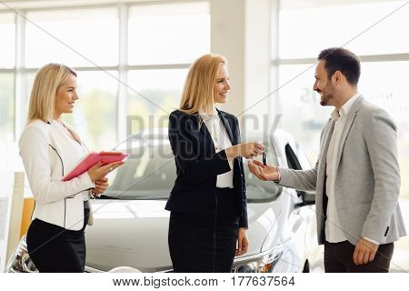 Beautiful salesperson selling cars at car dealership