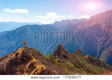 Happy Man in orange Jacket staying on Rock Cliff raising Hands Mountain Valley and Sun above Peaks on Background