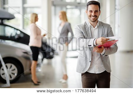 Salesperson at modern car dealership selling vehichles