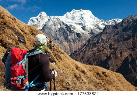 Unrecognisable Man from rear point of View staying with Backpack dressed in sporty Clothing observing Mountain Landscape