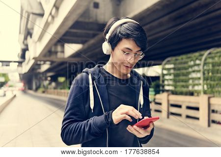 Asian guy listening music by headphones