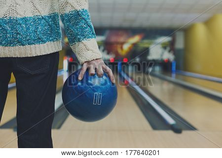 Unrecognizable man holds ball, prepare to throw it to bowling lane, closeup. Player plays active game. Cropped image of male leisure