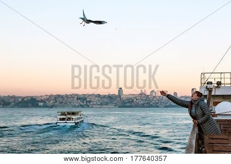 Woman feeding Sea Gulls from Board of Ferry floating across Bosphorus Harbor of Istanbul City soft sunrise colors of Sky and Urban landscape on Background