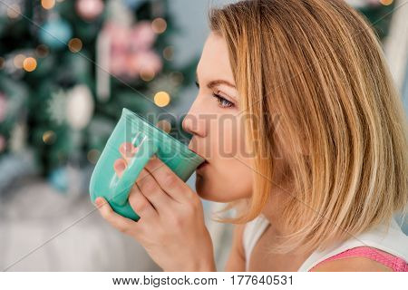 Beautiful woman with a cup of coffe in her hands with blured background looking away from camera