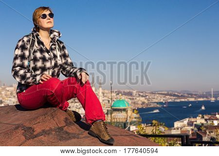 Lady in casual Clothing and old style Sunglasses sitting on the Roof of old Building in eastern City watching Urban Landscape and Sea Harbour