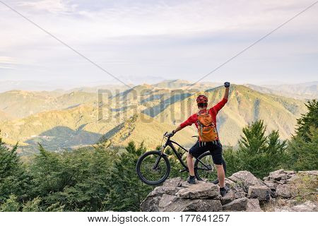 Mountain biker success looking at view on bike trail in autumn mountains. Celebrating beautiful inspirational landscape. Successful happy rider on rocks. Sport adventure motivation and inspiration.