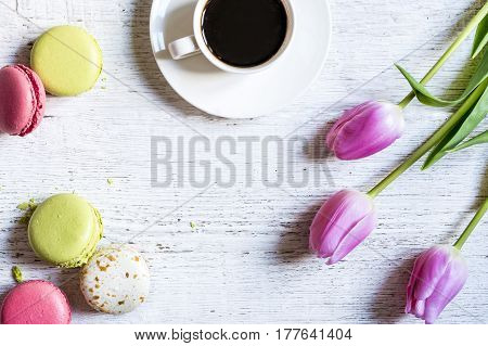Cup of coffee with pastry and flowers on a white table top view