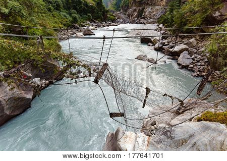 Broken Suspension Bridge in Himalayas Nepal. Looking at river in canyon forest and green trees. Annapurna Himal Range on Annapurna Circuit Trek. Autumn season in Nepal Asia.