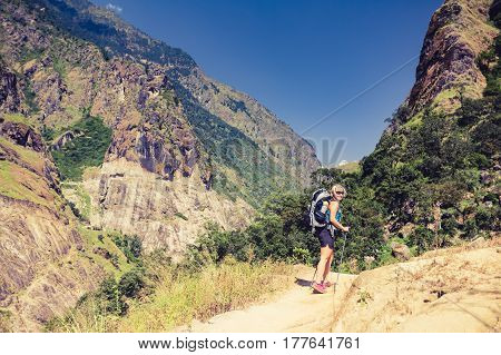 Woman backpacker climbing with backpack in Himalayas Nepal. Trekking and hiking with backpack in high mountains. Annapurna Himal Range on Annapurna Circuit Trek. Autumn season in Nepal Asia.