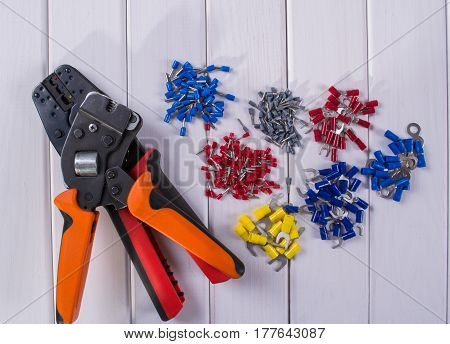 Cable lug in different colors and sizes on a white background. Tools for crimping.
