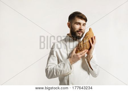 Handsome smiling BAKER smelling a freshly baked loaf in the kitchen of the bakery. Handsome smiling BAKER smelling a freshly baked loaf Oon white background.