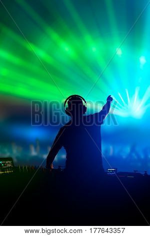 Charismatic disc jockey. Club disco DJ playing and mixing music for crowd people.