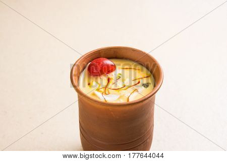 Authentic Indian cold drink made up of curd, milk & malai called Lassi in saffron / kesar flavour, also called kesariya or keshariya or kesar lassi, served in traditional indian terracotta glasses