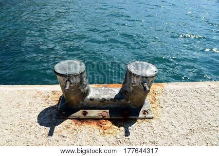 Metal berths for boats on the shore near the blue sea
