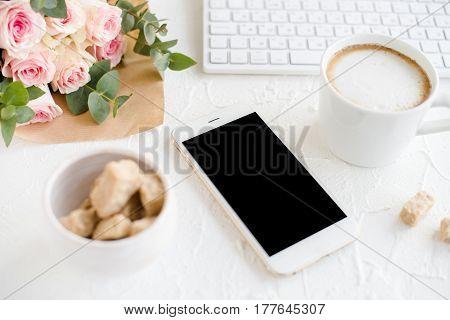 Romantic feminine background with coffee, smartphote mock-up and roses on white textured tabletop, elegant lady blogger workspace