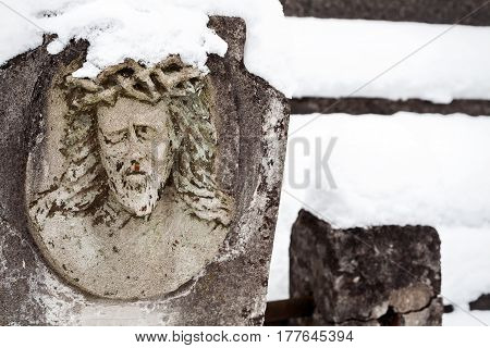 Face of Jesus Christ on old tombstone in winter