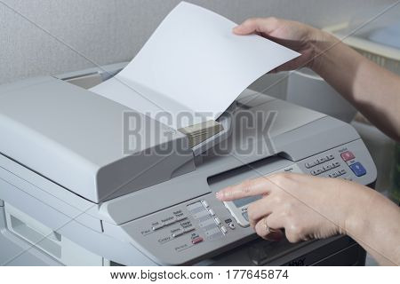 Midsection Of Businesswoman Using Fax Machine In Office