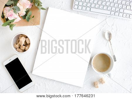 Romantic feminine background with coffee, smartphote, roses and magazine cover mock-up on white textured tabletop, lady blogger workspace