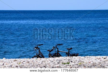 third bicycle on the beach near the blue sea