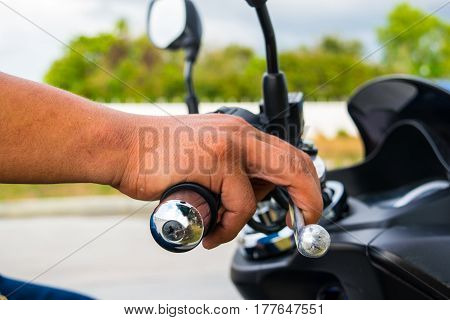 Human hand holds a motorcycle throttle control