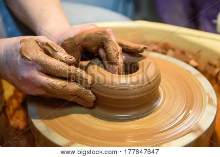potter makes a pot of clay, working on the potter's wheel.