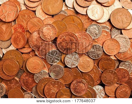 A pile of British coins consiting of coppers five pences and twenty pences.