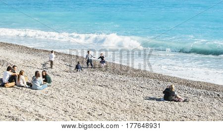 Nice, France - 25 February, A group of people of different ages on the shore, 25 February, 2017. People and tourists having a rest on the Cote d'Azur.