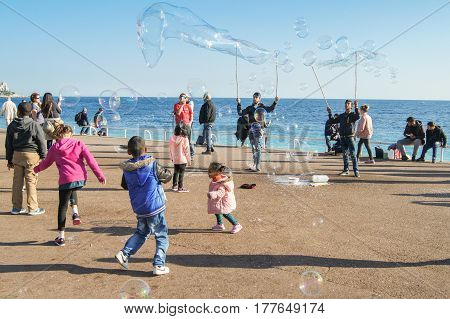 Nice, France - 25 February, Soap bubbles among people, 25 February, 2017. People and tourists having a rest on the Cote d'Azur.