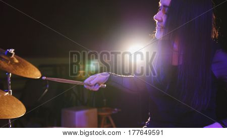 Girl rock musician - female drummer performing, telephoto