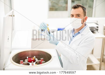 Hispanic Male Chemist Using Centrifuge