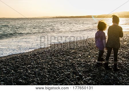Nice, France - 25 February, Two girls by the sea at sunset, 25 February, 2017. People and tourists having a rest on the Cote d'Azur.