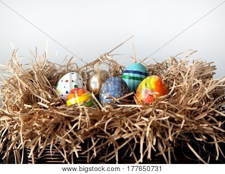 Easter colorful eggs in the nest on white background
