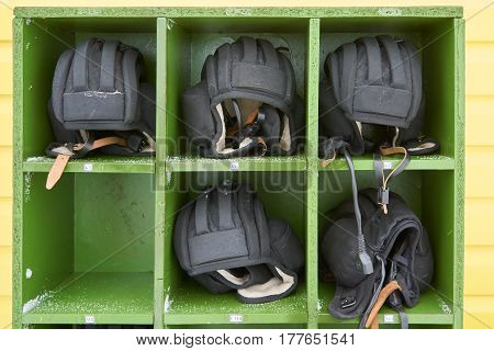 Russian tank winter helmets placed in order in green wooden box on military training ground. Russian abreviation KT means tank commander MB means driver mechanic of the tank crew.