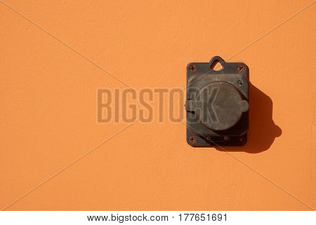 External power outlet on beige wall outdoors