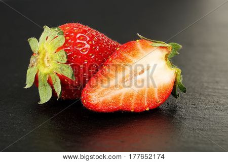 whole and half a strawberry on black stone