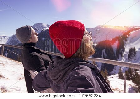 two young men sitting on bench and enjoying the sun surrounded by mountain peaks