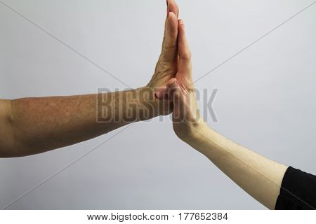 Two female hands high fiving on white background