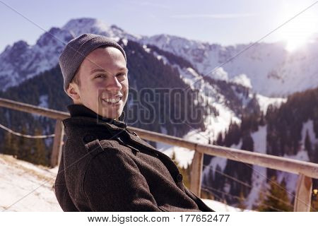 young man sitting in the sun surrounded by snowy mountains and looking at camera