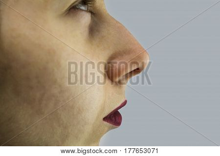 A human female nose up close sniffing