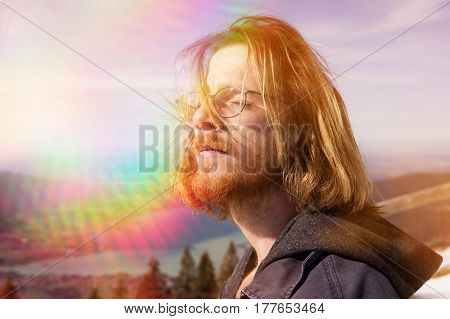 young bearded red-haired man enjoying the sun with mountains and lake in the background